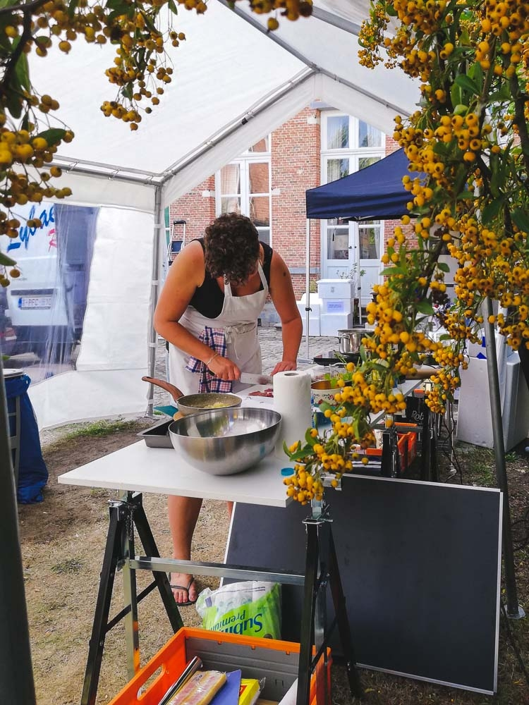 food stylist Eveline Boone working in outside kitchen under a partytent