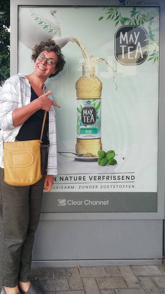Eveline Boone in front of a billboard with May Tea advertising pointing at her food styling work