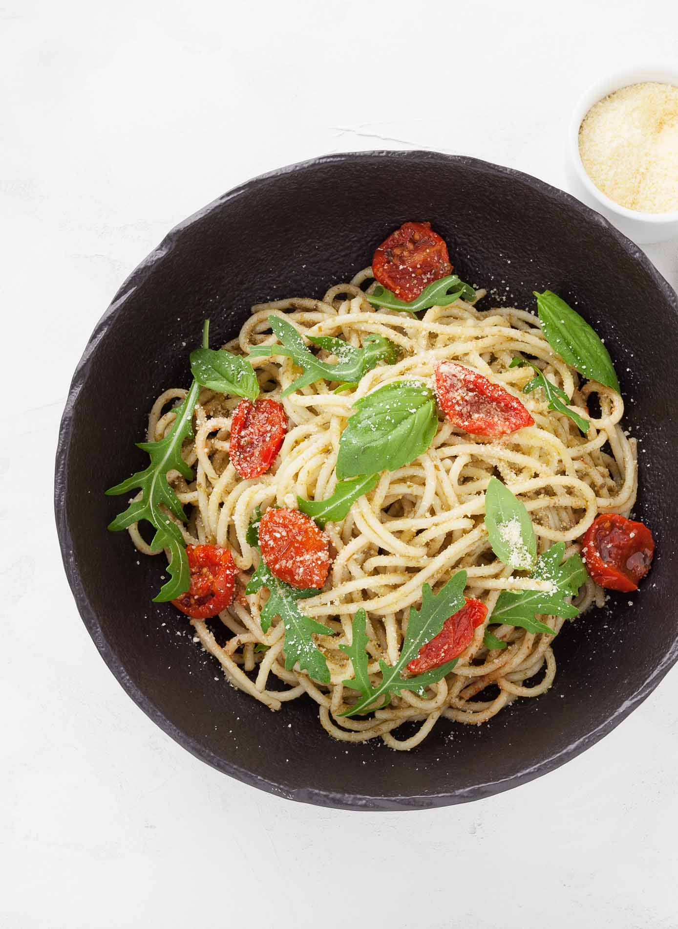 spahgetti with dried tomatoes basil and parmigiana in a black bowl in a restaurant