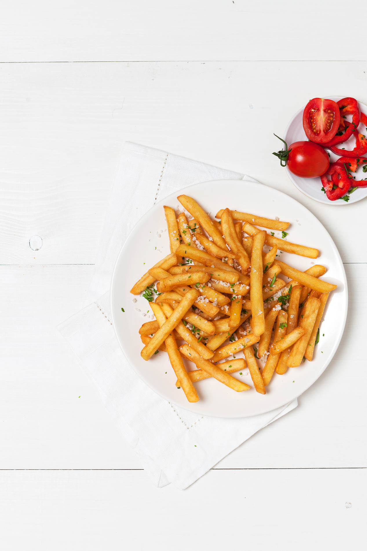 white plate with fries on a white wooden table with tomatoes