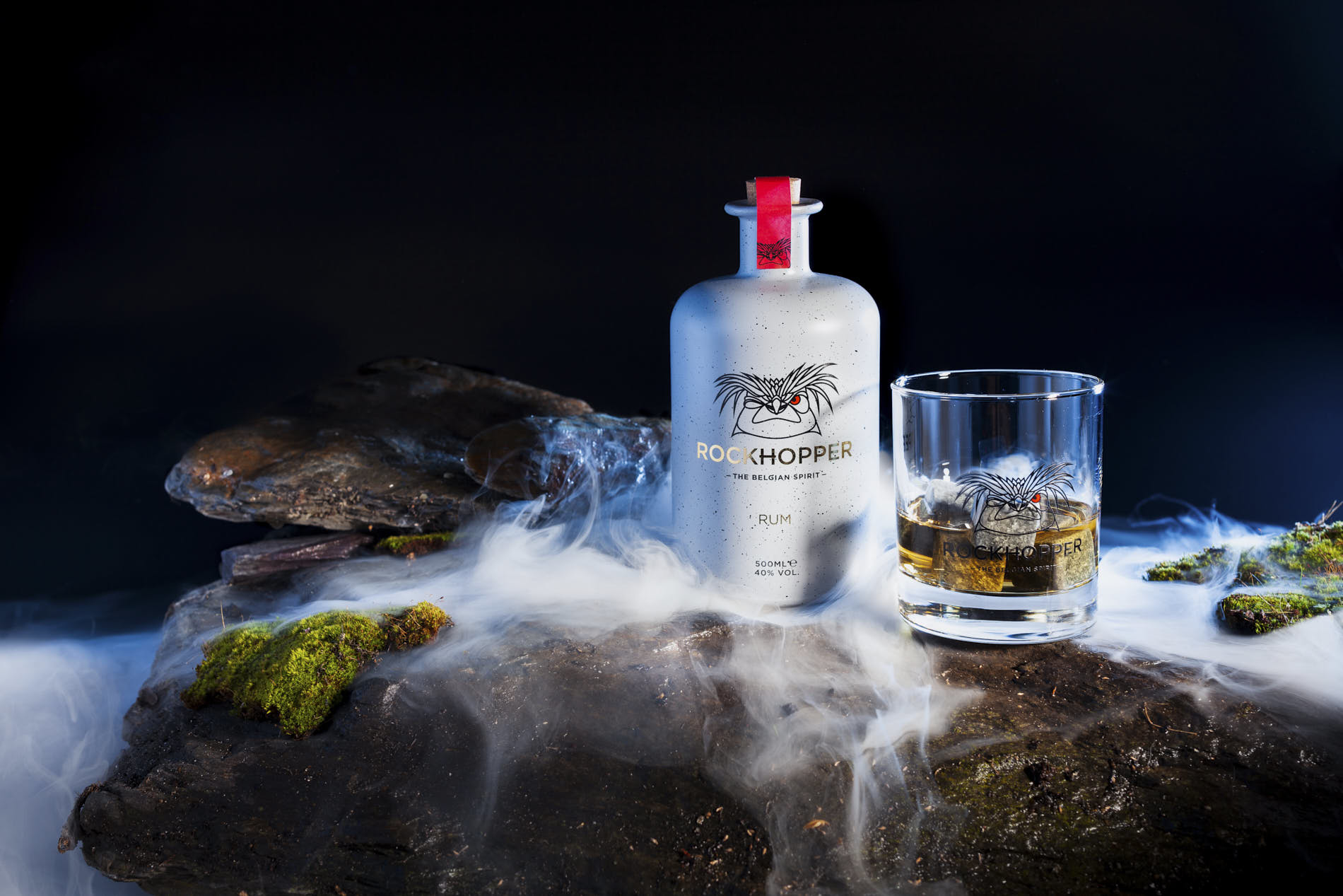 bottle of rockhopper rum and a glass on foggy stones