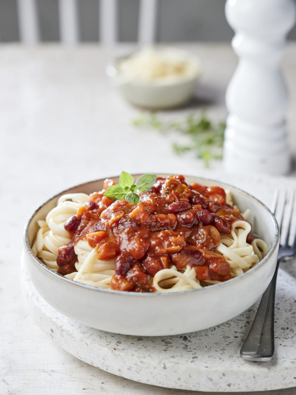 White Bowl Of Tagliatelle With Tomato Sauce With Vegetables On A White Table With White Peppermil