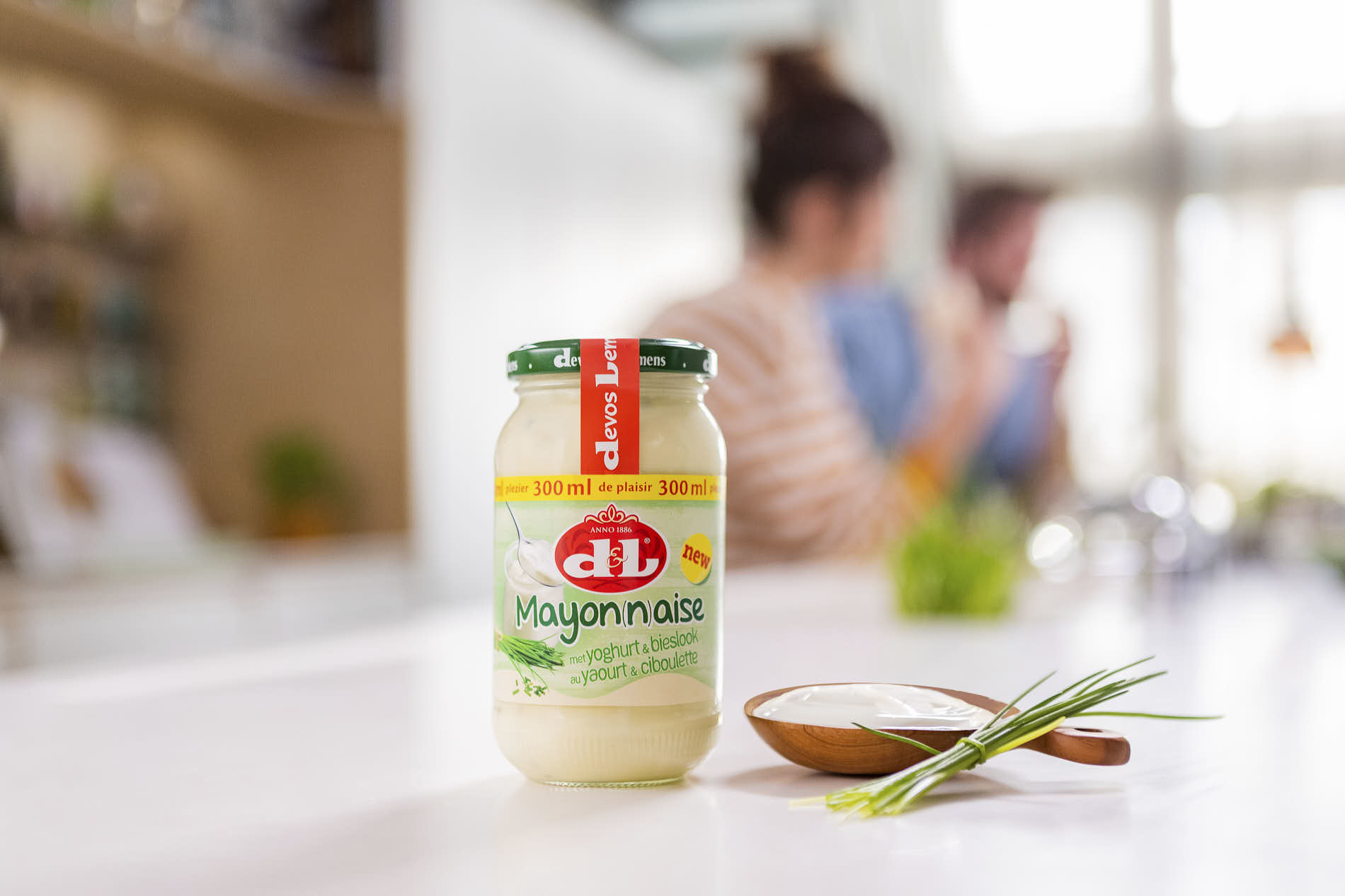 product shot of a Devos&Lemmens mayonaise jar with blurred people in the background of the kitchen