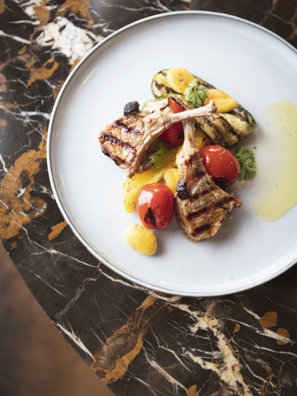 Photo Of Lamchops And Grilled Vegetables On A White Plate And Brwon Marble Background In A Workshop Space