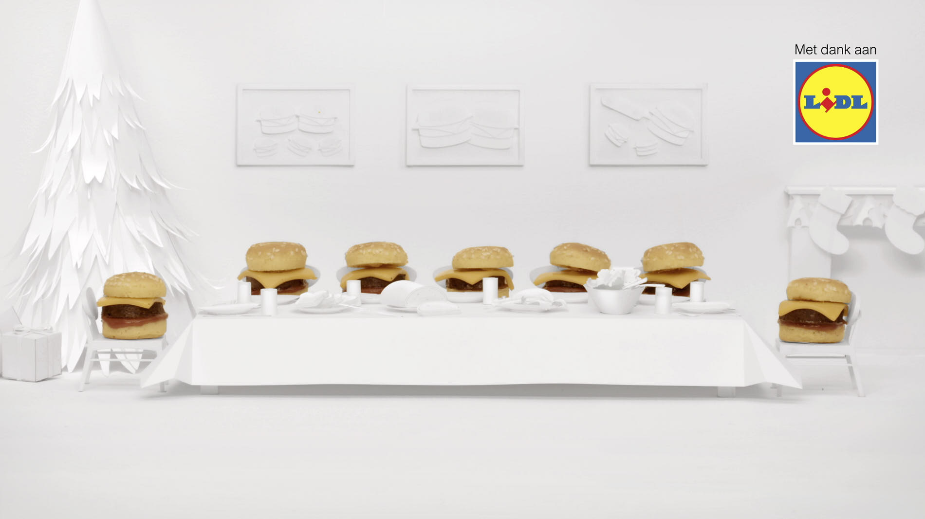 white paper miniature setting of a dinner table and mini-hamburgers sitting on chairs