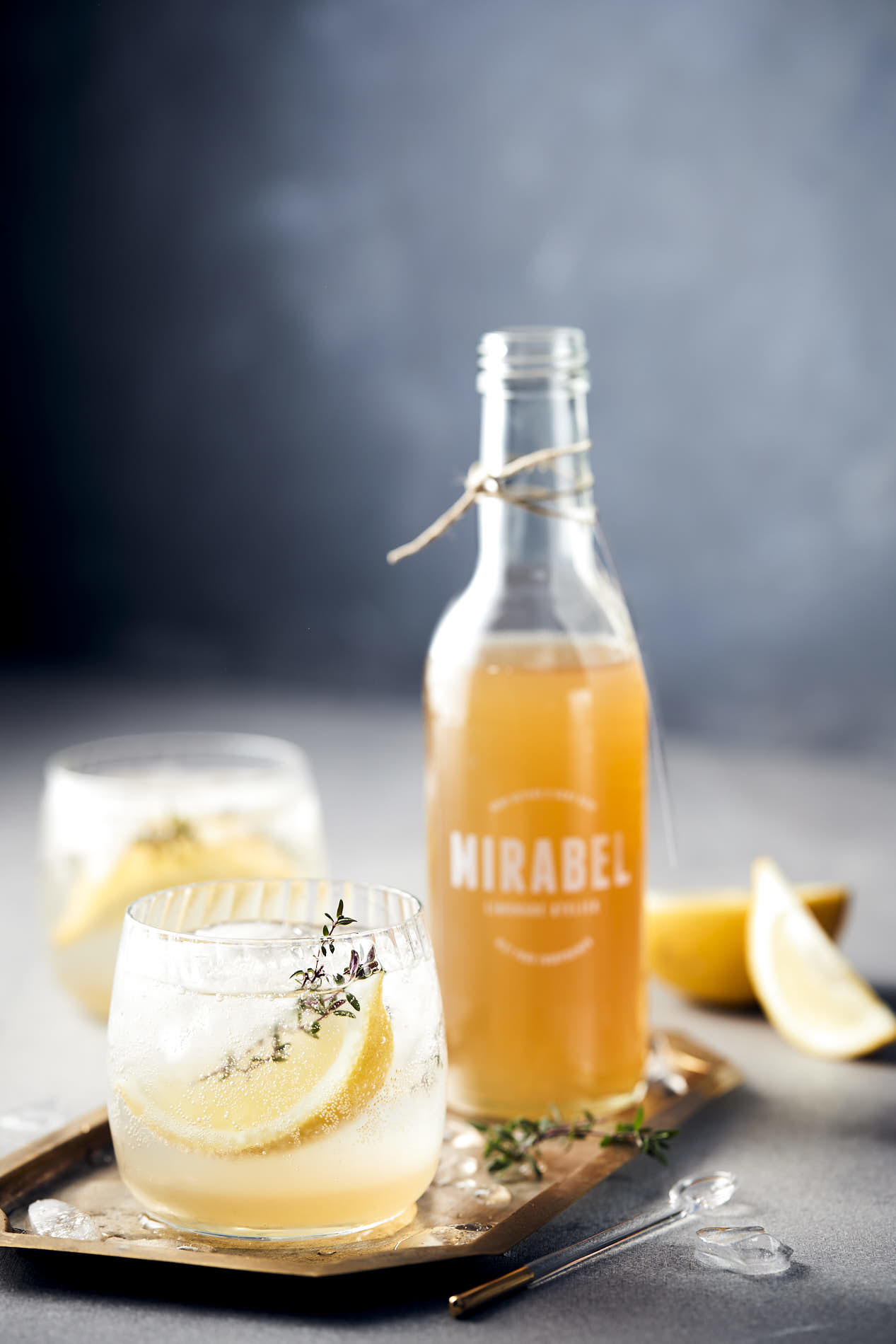 food photo by French Beans of a bottle of lemon-thyme syrup by Mirabel with two glasses of lemonade