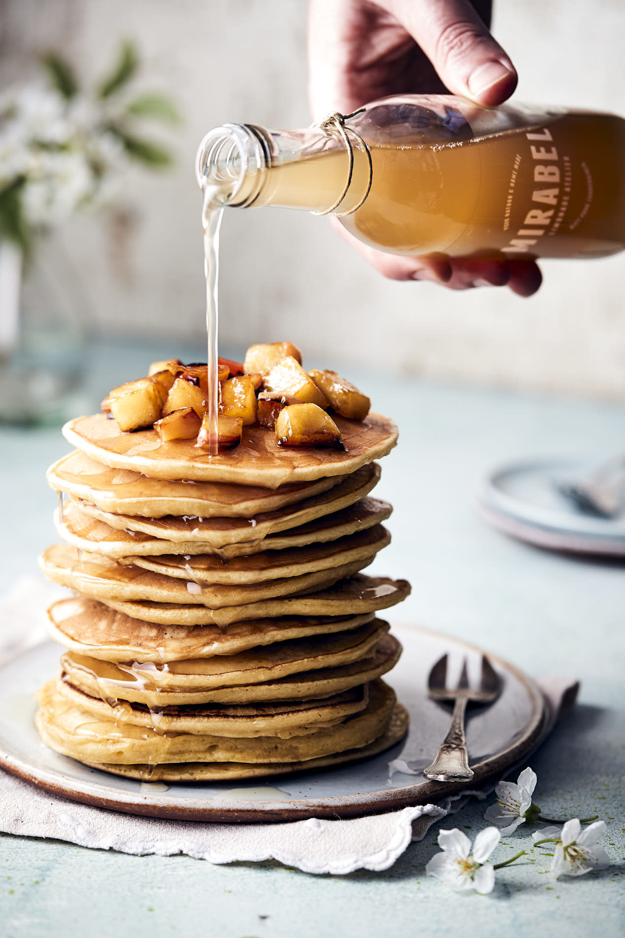 stack of american pancakes with Mirabel apple-cinnamon syrup in a food photo by French beans