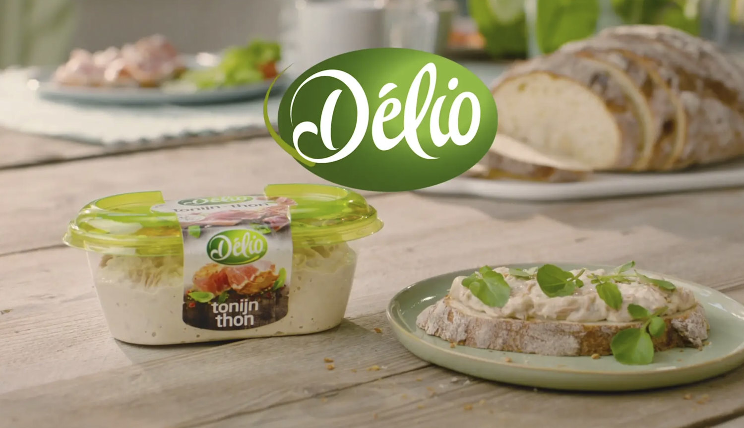 container of délio tuna salad on a rustic wooden table with slice of bread and tuna salad spread on it