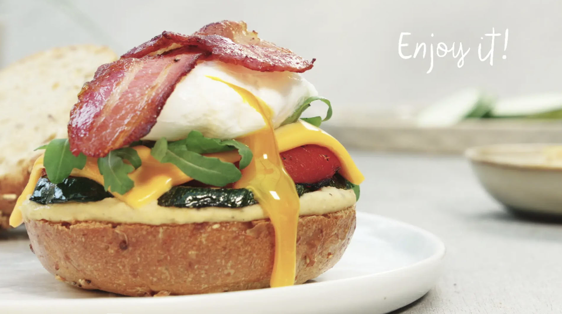 still from recipe video of a sandwich with grilled vegetables bacon and poached egg