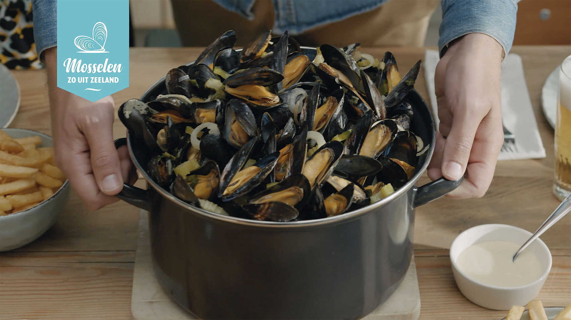 man putting down a pot of mussels on the table