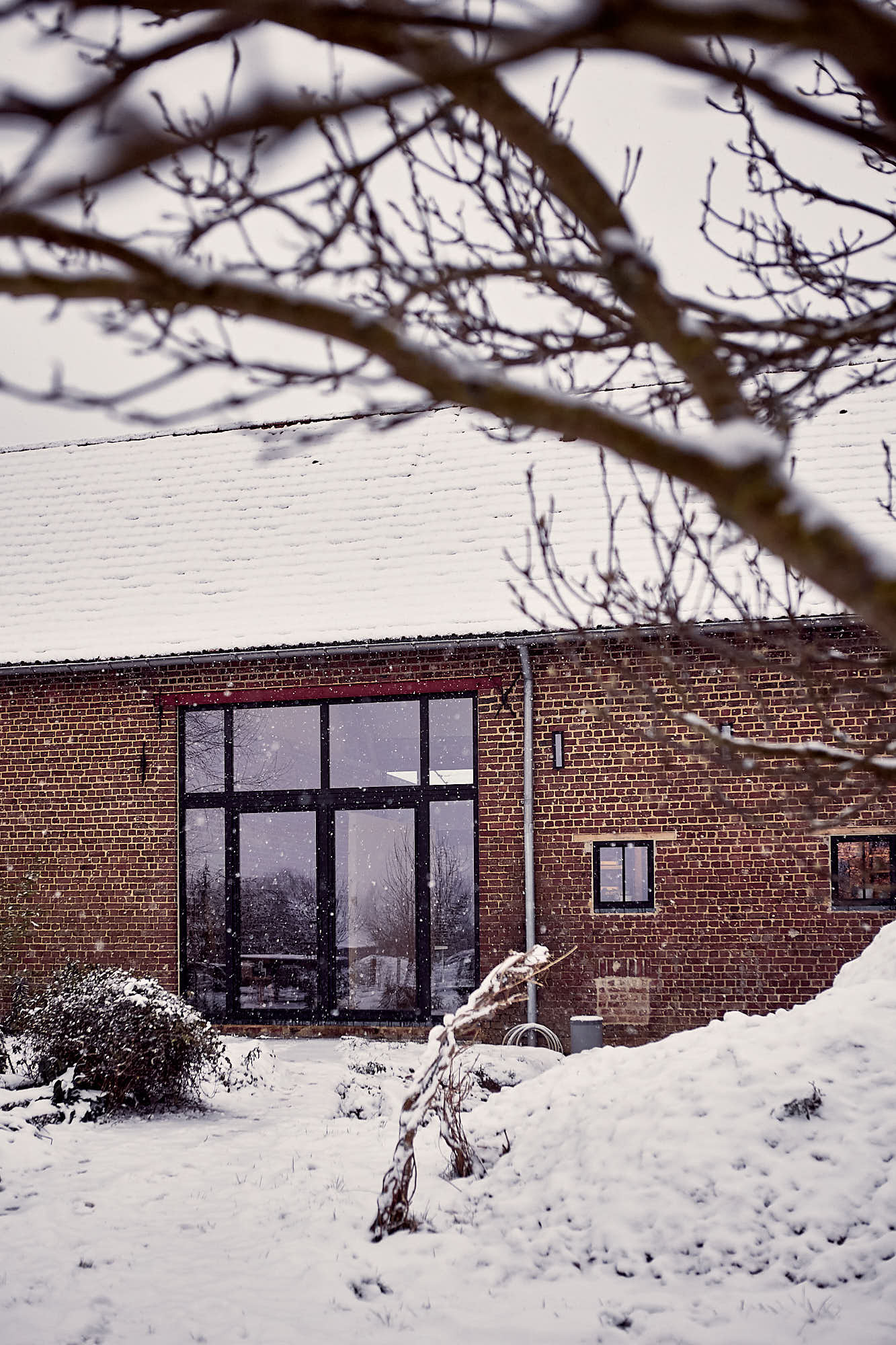 rustic farm with large window in a snowy landscape