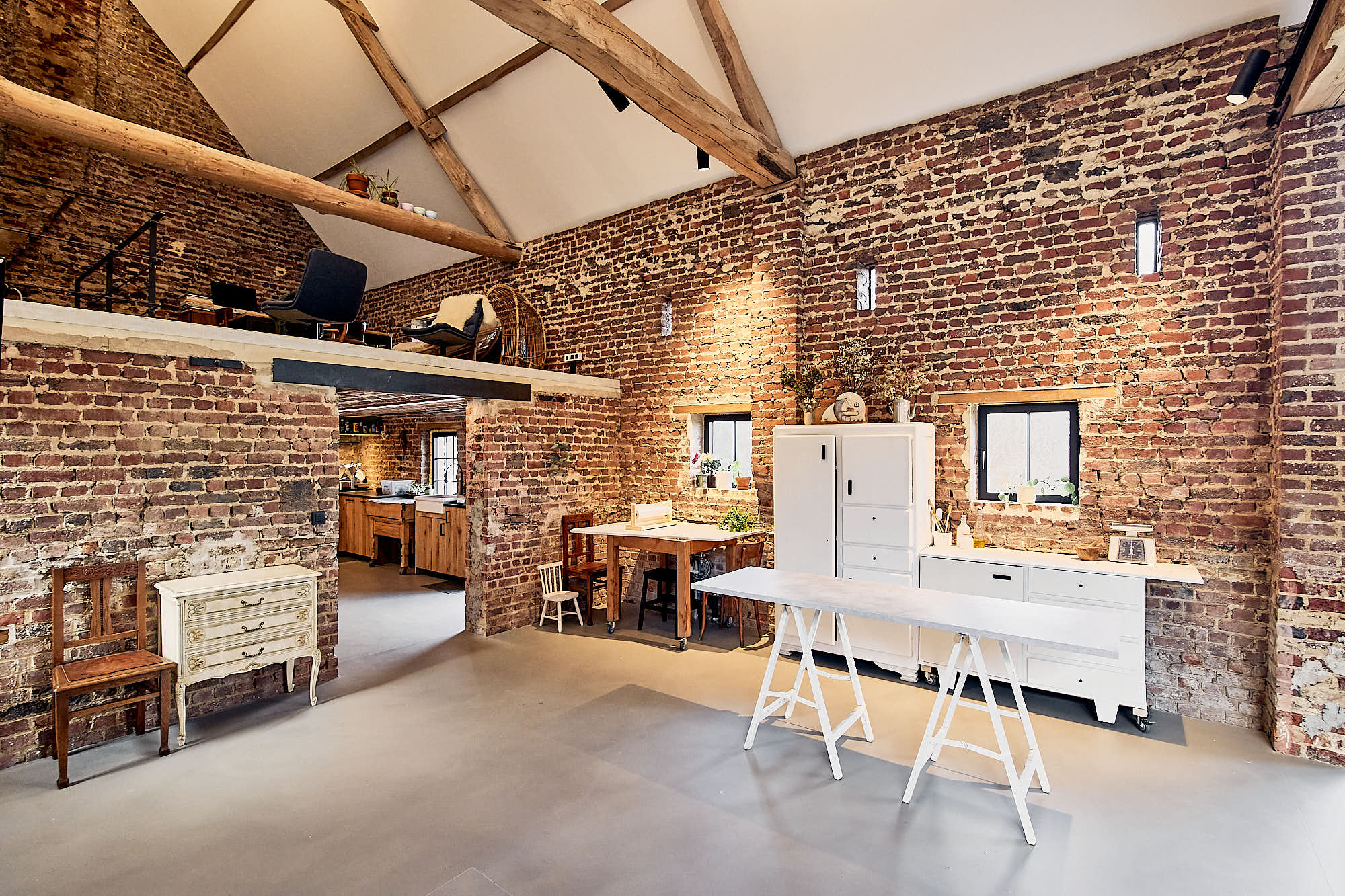 Modular Set Furniture In A Rustic Studio Space And A Kichen In The Background
