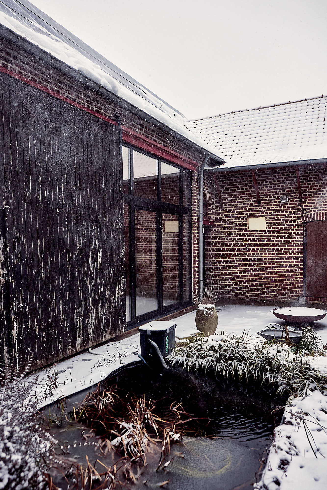 courtyard and pond with a farm surrounding it in the snow